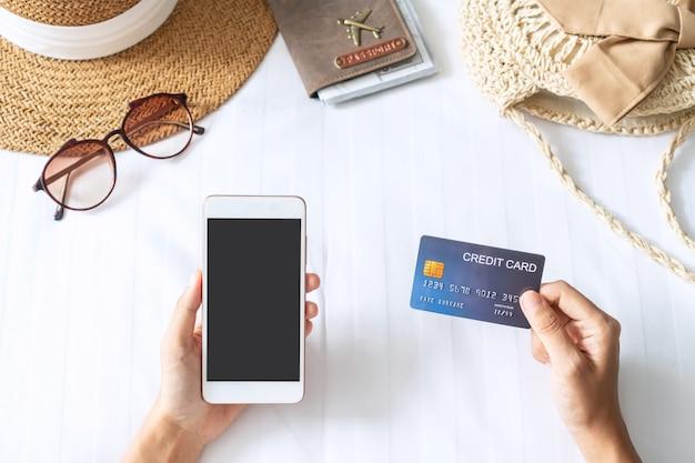 Hand, die kreditkarte hält, während smartphone mit reiseartikeln auf bett verwendet wird