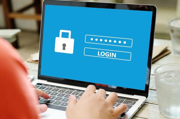 Hand, die laptop-computer mit passwortanmeldezeichen auf schirm, cybersicherheitskonzept bindet