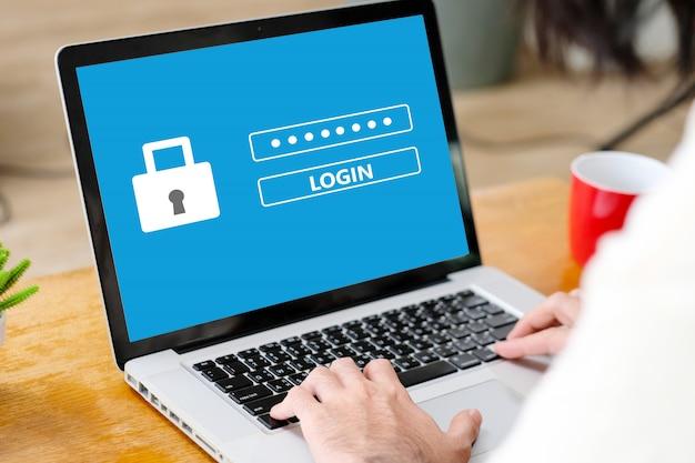 Hand, die laptop-computer mit passwortanmeldung auf schirm schreibt