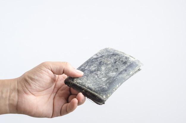 Hand, die leere alte ledertasche oder manngeldbörse mit form und pilz hält