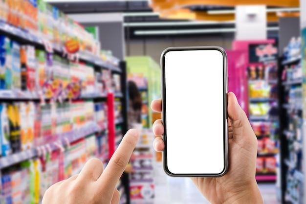Hand, die leere form des mobiltelefons mit supermarkt- oder einkaufszentrumhintergrund hält. online-shopping oder e-commerce-konzept.