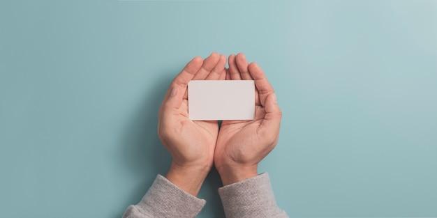 Hand, die leere geschäftsnamenskarte auf blauem hintergrund mit kopienraum für eingabetext und infografik-symbol hält.