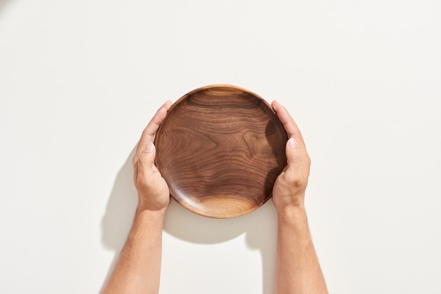 Hand, die leere hölzerne platte lokalisiert auf weiß hält
