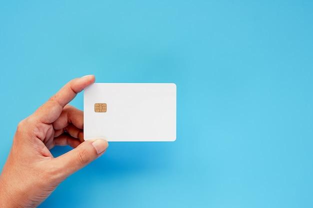 Hand, die leere kreditchipkarte auf blauem hintergrund hält