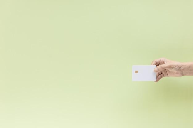 Hand, die leere kreditchipkarte auf grünem hintergrund mit kopienraum hält