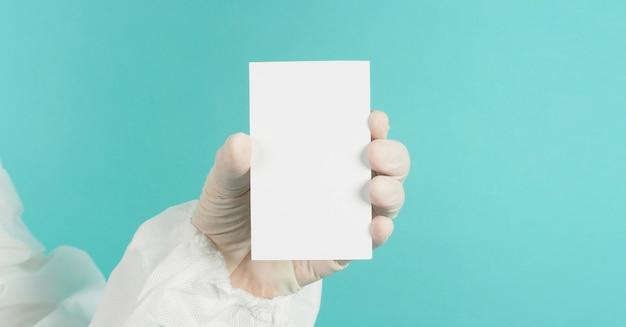 Hand, die leere leere weiße karte hält. hand mit ppe-anzug, latexhandschuh auf grünem oder blauem hintergrund tiffany. leerer platz für text