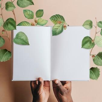 Hand, die leere notizbuchseite mit grünen blättern hält