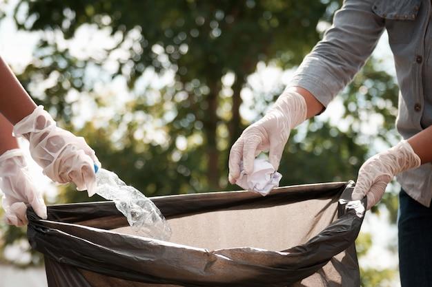Hand, die leere plastikflasche herein zur abfallschwarztasche einsetzt