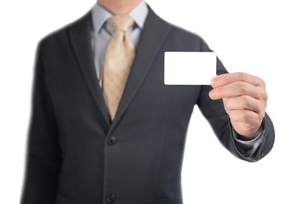 Hand, die leere visitenkarte hält. hübscher geschäftsmann im schwarzen anzug, der seine modellkreditkarte zeigt, um eine zahlung zu machen. mann, der leere visitenkarte oder visitenkarte hält und zeigt. isoliert auf weiß