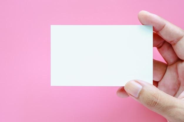 Hand, die leere visitenkarten auf rosa hintergrund hält