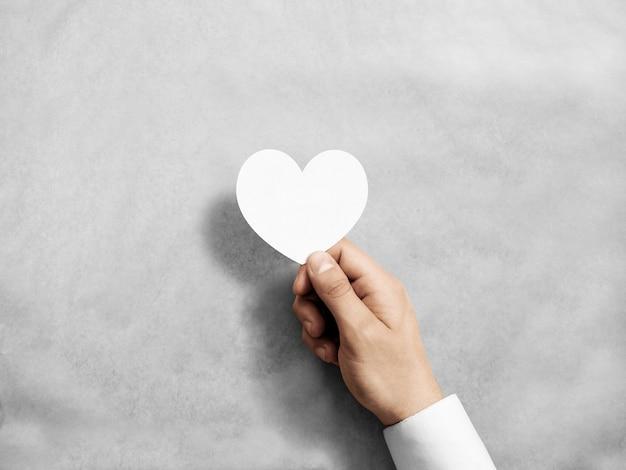 Hand, die leere weiße valentinskarte hält