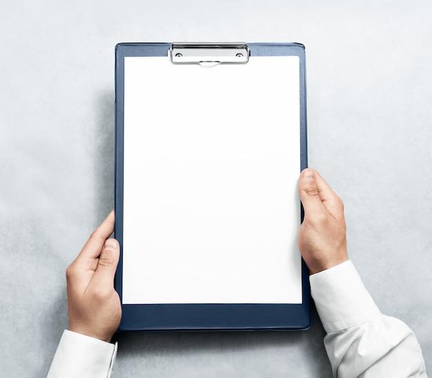 Hand, die leere zwischenablage mit weißem a4-papierentwurf hält