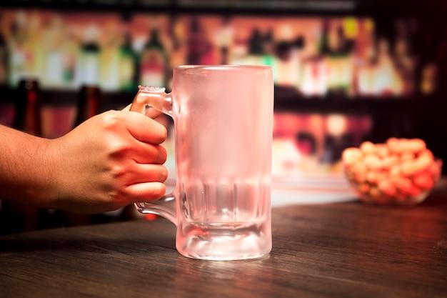 Hand, die leeres bierglas hält