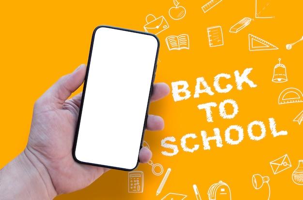 Hand, die leeres smartphone auf briefpapierschule kritzeleienhintergrund hält