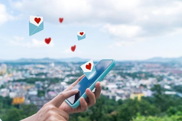 Hand, die liebesbrief-e-mail in der online-community des sozialen netzwerks des smartphones mit liebesbrief-e-mail der sozialen medien tippt, sendet symbole zum valentinsgrußkonzept aus.