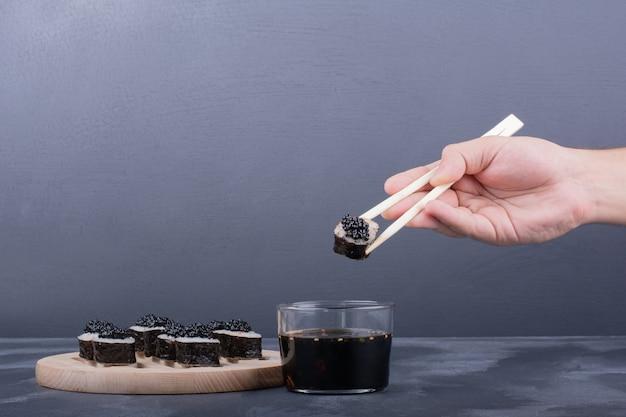 Hand, die maki-sushi-rolle mit stäbchen auf marmor hält.