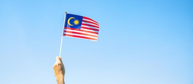 Hand, die malaysia-flagge auf hintergrund des blauen himmels hält. nationalfeiertag im september und unabhängigkeitstag im august