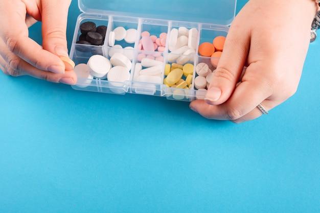 Hand, die medizinkasten mit pillen zeigt