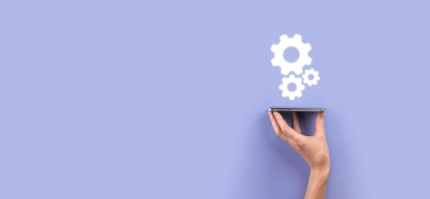 Hand, die metallzahnräder und zahnräder hält, die das konzept der interaktionsteamarbeit darstellen, hand halten gruppe von virtuellen zahnrädern