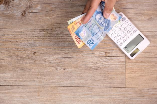 Hand, die mexikanisches geld mit taschenrechner auf holztisch hält