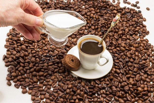 Hand, die milch in eine tasse kaffee und körner rundum auf weißem hintergrund gießt