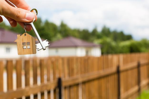 Hand, die miniaturhaus und schlüssel hält