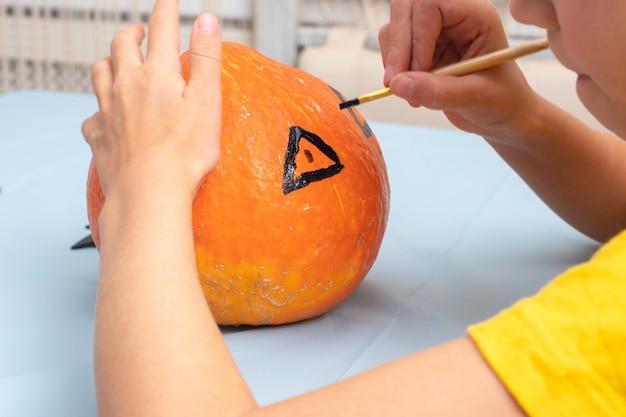 Hand, die mit einem pinsel ein gruseliges gesicht auf einen orangefarbenen kürbis zeichnet, um eine halloween-jack-laterne zu erstellen, nahaufnahme. halloween-party und familienlebensstil-hintergrund