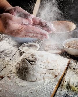 Hand, die mit mehl auf teig über der tabelle abwischt