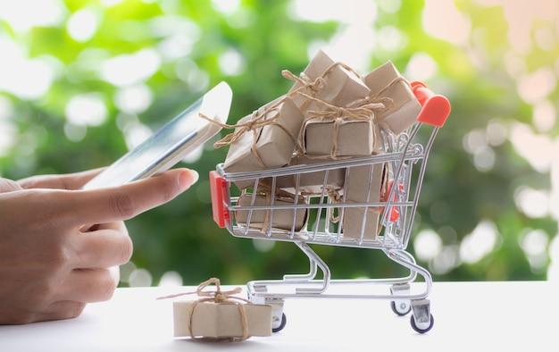 Hand, die mobile und geschenkboxen in einem warenkorb hält