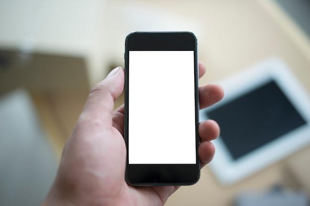 Hand, die mobiltelefon mit anderem gerät hält