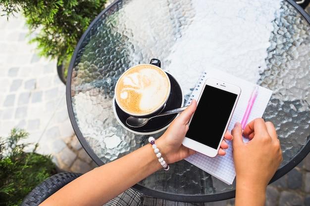 Hand, die mobiltelefon mit kaffeetasse auf glastisch hält