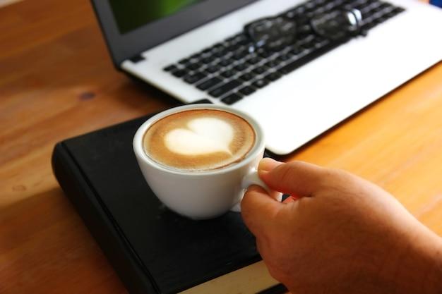 Hand, die morgenkaffee in der entspannungszeit hält. herzformoberfläche auf weißer kaffeetasse auf schwarzem buch mit bürobedarf