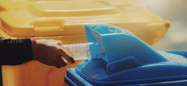 Hand, die müllflaschenplastik hält, das zum reinigen in den müll legt