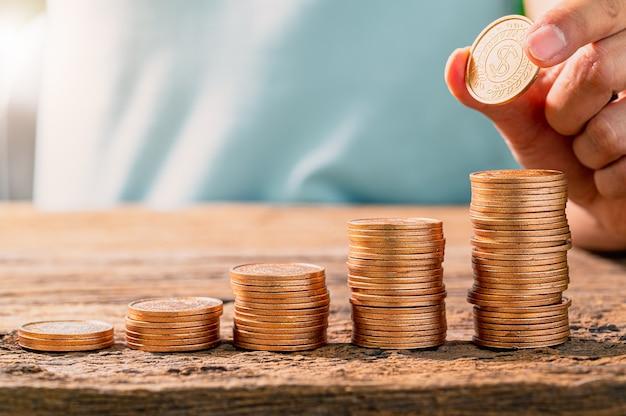 Hand, die münze auf münzstapel legt
