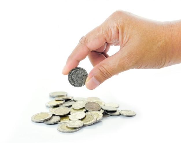 Hand, die münze auf weißer wand hält