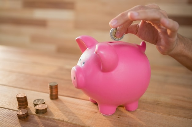 Hand, die münze in piggy bank