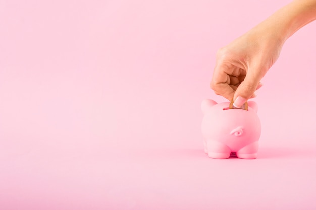 Hand, die münze in rosa sparschwein setzt