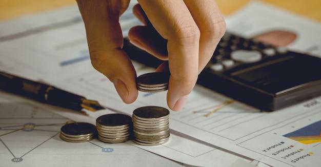Hand, die münzen und das stapeln auswählt. es gibt taschenrechner und stift daneben. geringe schärfentiefe. fokus an der fingerspitze.