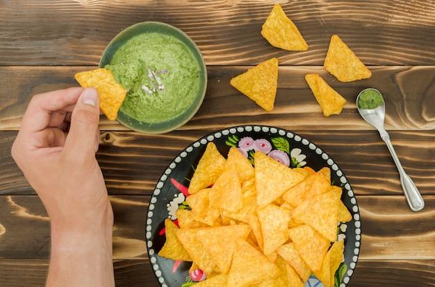 Hand, die nachos in guacamole eintaucht