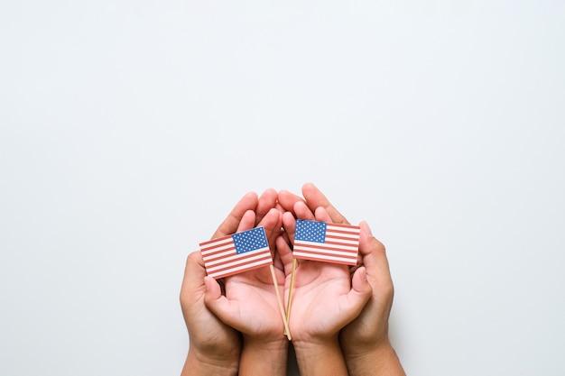 Hand, die nationale amerikanische miniflagge hält und berührt. konzept zum weltveteranentag