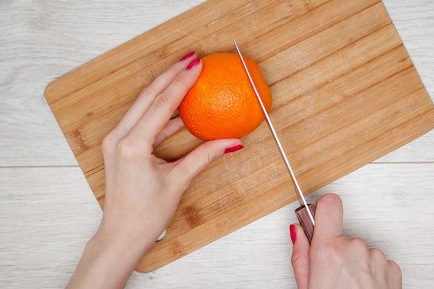 Hand, die orange auf hölzernem brett schneidet