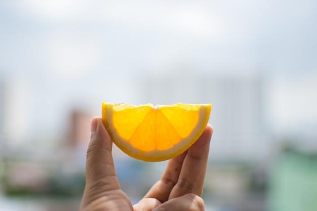 Hand, die orange scheibe mit himmel hält. weicher fokus.