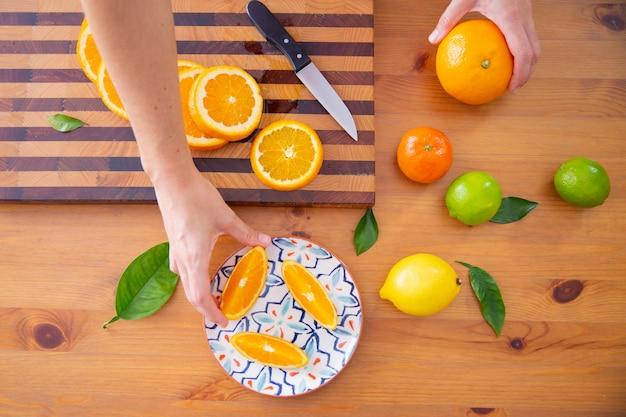 Hand, die orange stück von der keramikplatte nimmt