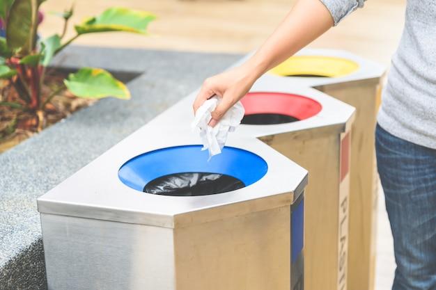 Hand, die papierabfall in abfallabfall, mit vorgewähltem fokus einsetzt