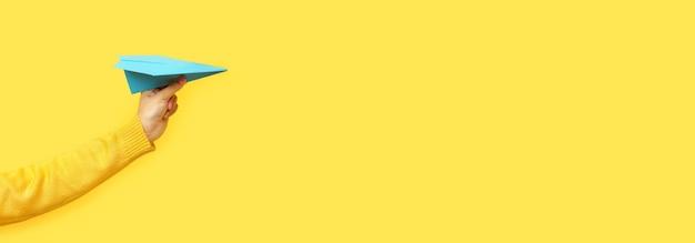 Hand, die papierflugzeug über gelbem raum hält