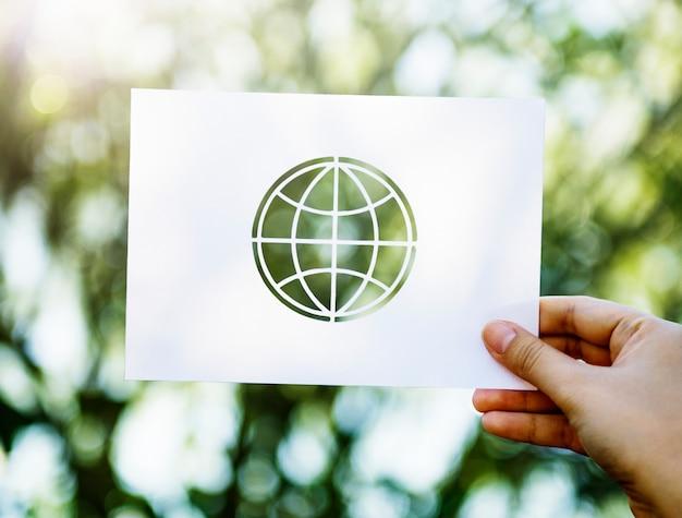 Hand, die perforiertes kugelformpapier auf grünem naturhintergrund zeigt