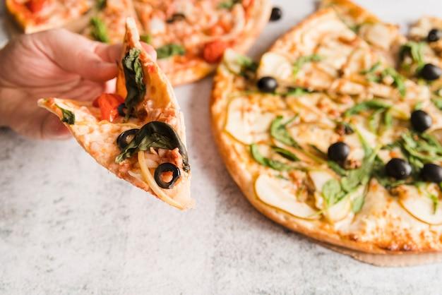 Hand, die pizzascheibe nimmt