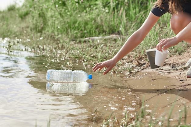 Hand, die plastikflaschenreinigung am flussstrand aufnimmt. freiwilliger, der den müll aufräumt. stoppen sie plastik. recycling.