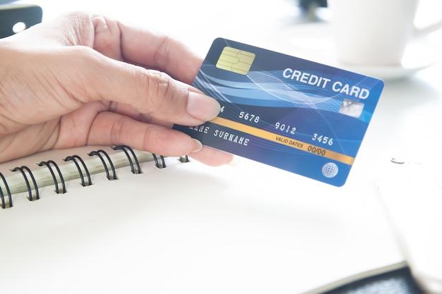 Hand, die plastikkreditkarte hält. e-payment, technologie und online-shopping-konzept