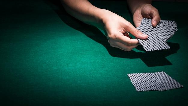 Hand, die pokerkarte auf grüner kasinotabelle hält